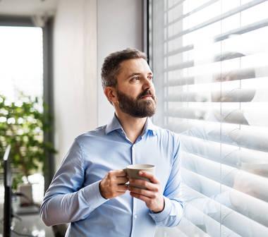 Mann sieht aus dem Fenster